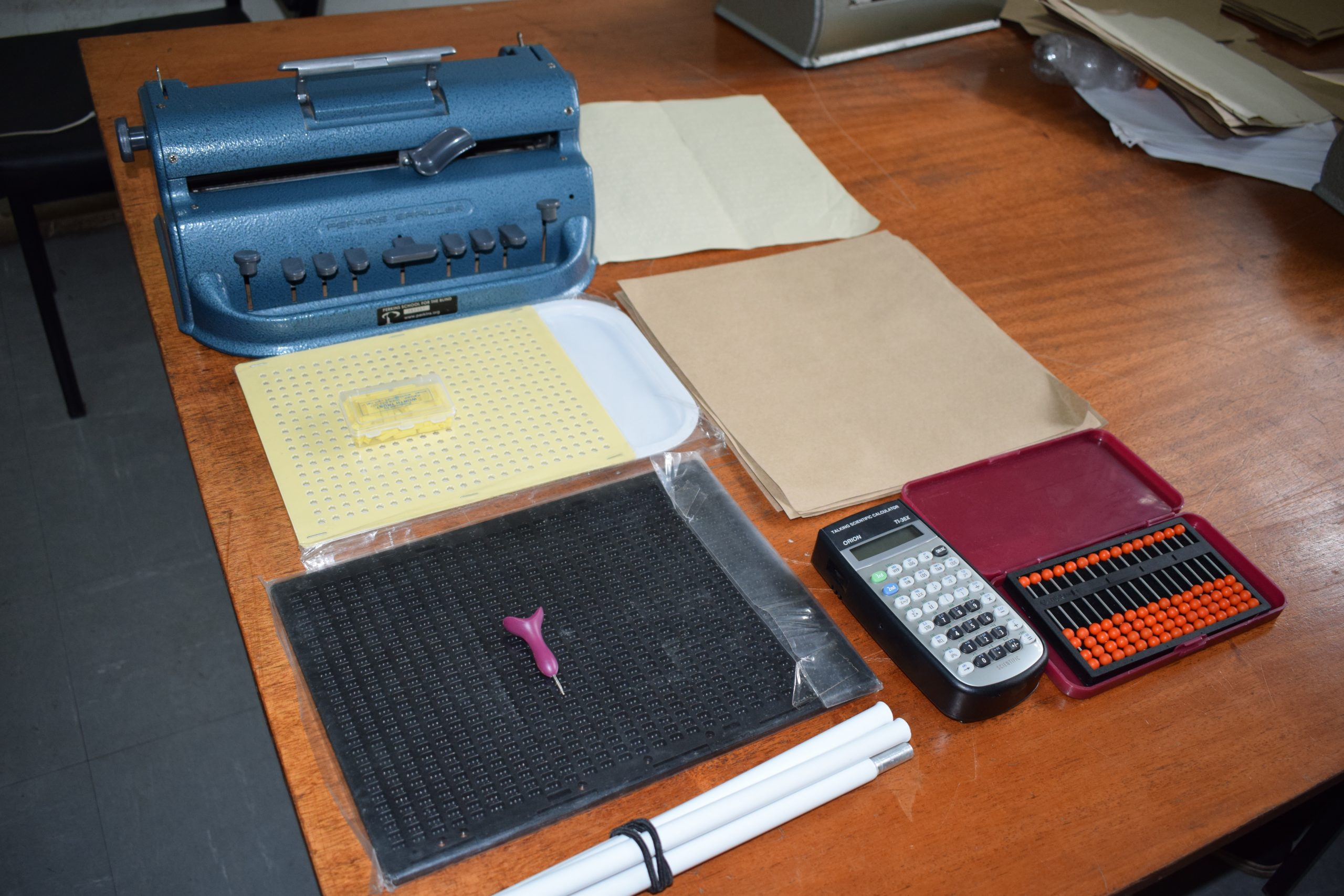 a picture of braille machine,stylus pen,talking calculator,peg board, Abacus, white cane